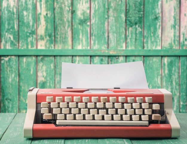 Red typewriter on a green rustic wall