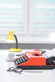 Red typewriter with lamp and coffee on white office desk near the window