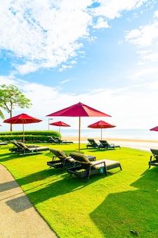 Красный зонт и шезлонг с фоном морского пляжа и голубым небом и солнечным светом