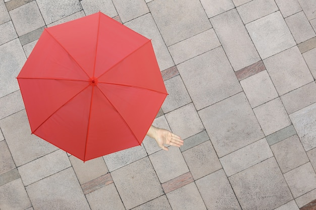 Red umbrella and a hand of man standing on stone floor and hand protruding outside.