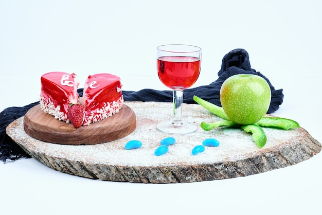 A red valentine cake with a glass of drink.