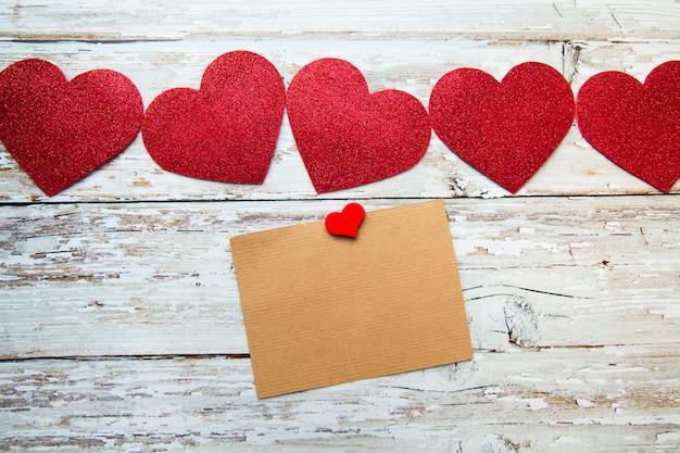 나무 배경에 텍스트 카드와 함께 빨간 발렌타인 하트. 발렌타인 데이. 평면도