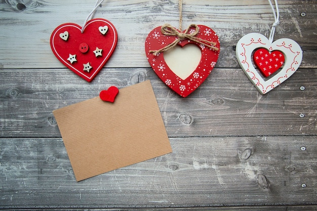 Red valentine hearts with a card for text on a wooden background