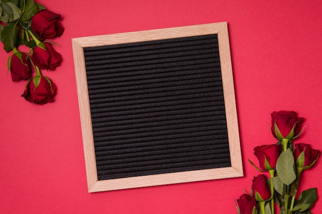 Red valentine's day background, empty letter board with red roses.