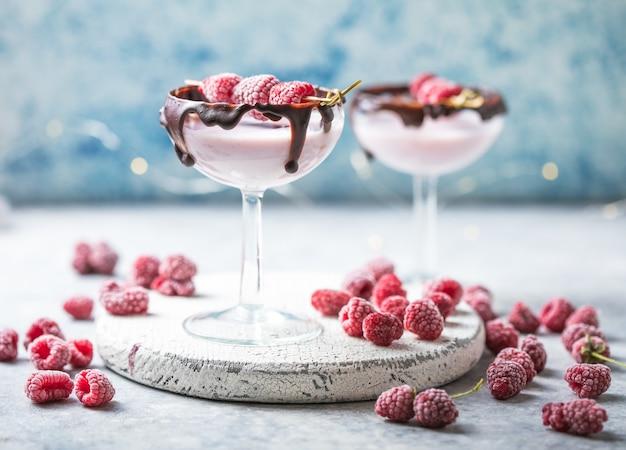グラスに入った赤いバレンタインデーのカクテル。ラズベリー入り飲料