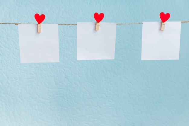 Red valentine's love hearts pins hanging on natural cord against blue background. mock up concept for your text