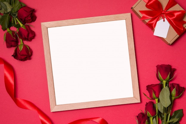 Red valentines day background wit empty frame and red roses.