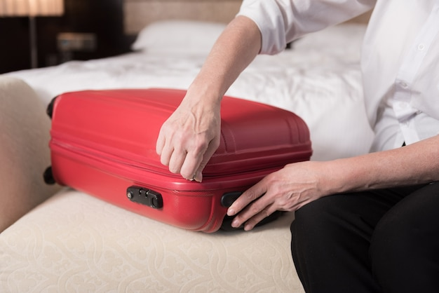 Red valise. modern big red valise lying on the couch and aged woman touching it