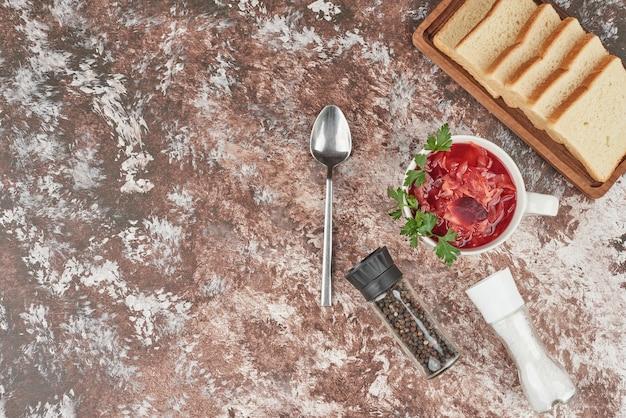 ハーブと白いカップの赤い野菜スープ。