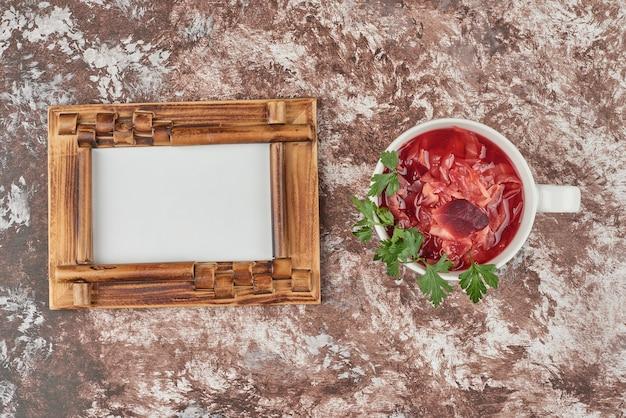 白いカップの赤い野菜スープ