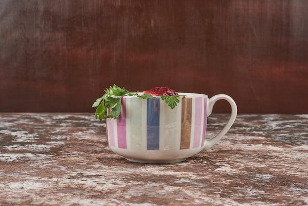 Zuppa di verdure rossa in una tazza bianca con erbe aromatiche.