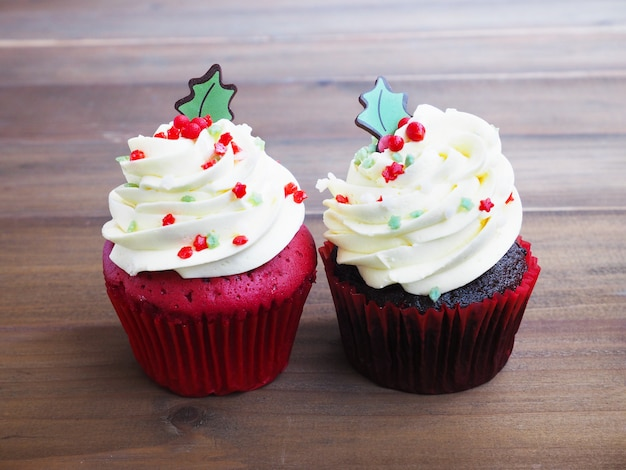 Red velvet and black forest cupcakes in christmas tree shape on wooden table background.