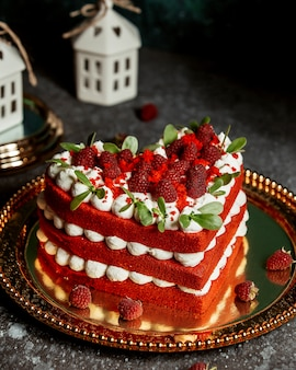 Red velvet cake in heart-shape garnished with raspberries and mint leaves