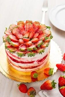 Красный бархатный торт на белой деревянной предпосылке. с клубникой.