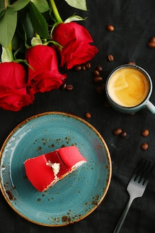 Red velvet cake on plate with cup of coffee and red rose top view
