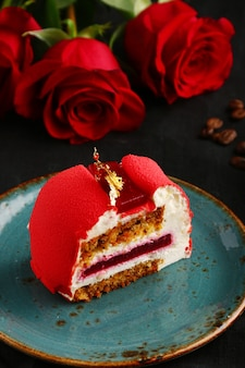 Red velvet cake on plate with cup of coffee and red rose.