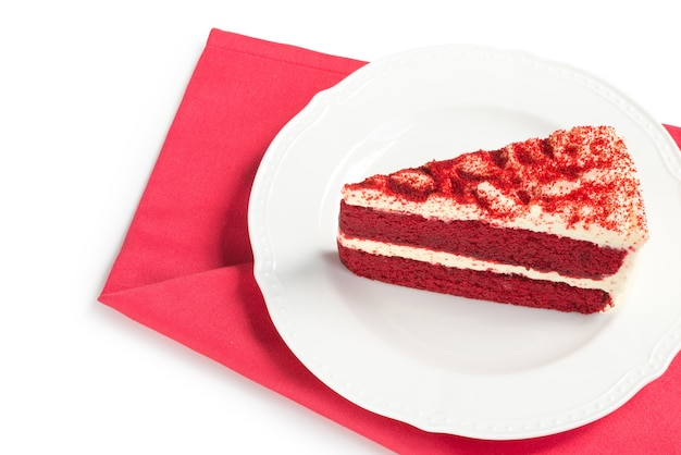 Red velvet cake sliced in piece on white plate over red placemat