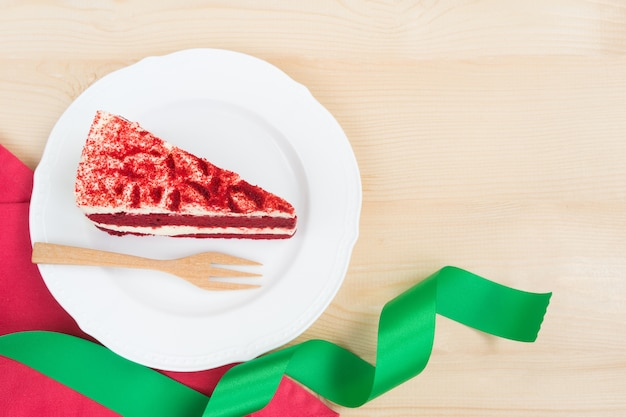 Red velvet cake sliced in piece on white plate on wood background and copy space for x'mas