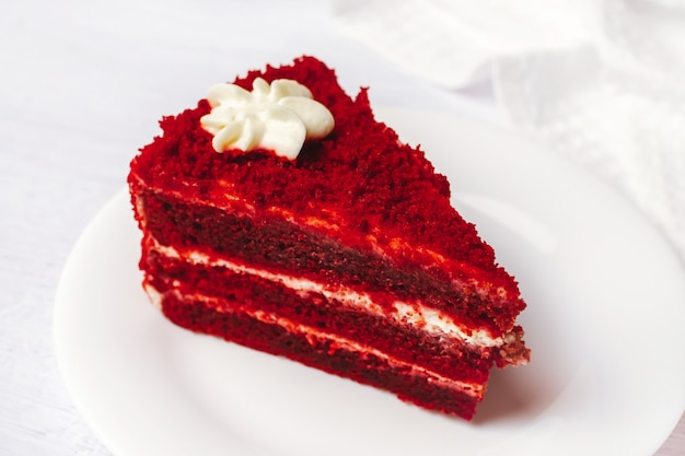 Red velvet cake sliced in piece on white plate