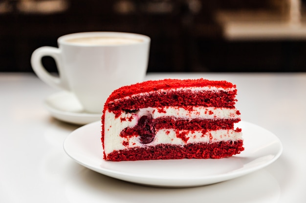 Red velvet cake with cherry on a white plate and a cup of coffee