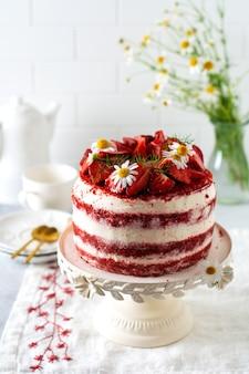 회색 배경에 흰색 보드에 딸기, 휘핑크림, 데이지 꽃다발을 넣은 레드 벨벳 케이크. 발렌타인 데이, 웨딩 디저트 또는 생일 파티. 베이커리, 제과 개념입니다. 공간을 복사합니다.