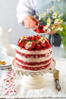 Красный бархатный торт с клубникой, взбитыми сливками и букетом ромашек на белой доске на сером фоне. день святого валентина, свадебный десерт или день рождения. пекарня, концепция кондитерских изделий. скопируйте пространство.
