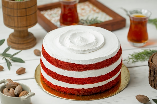 Red velvet cake with white whipping cream and glass of tea.
