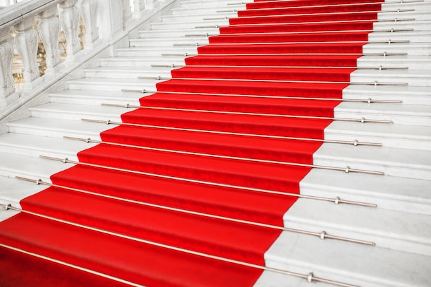 Red velvet carpet. climb the stairs. prestigious nomination. stairway go up. business success. stairs covered with red carpet. velvet fabric.