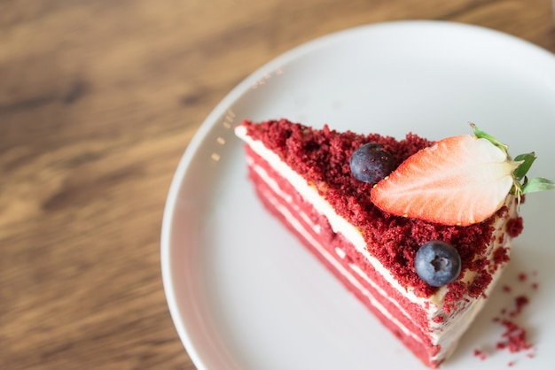 Red velvet cheesecake on wooden table in cafe.