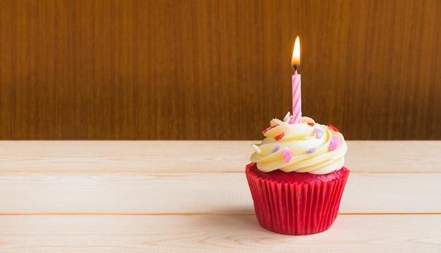 Red velvet cup cake with candle light over light wood board