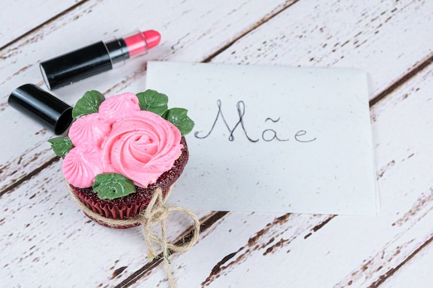 Red velvet cupcake with butter cream icing, next to a lipstick and note written in portuguese, mother.