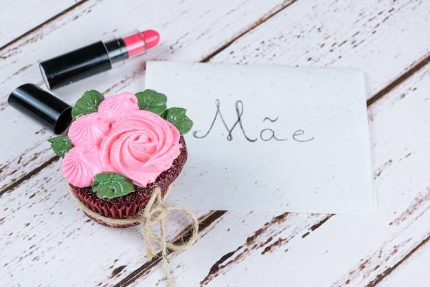 Красный бархатный кекс с глазурью из сливочного крема, рядом с губной помадой и запиской на португальском, мама.