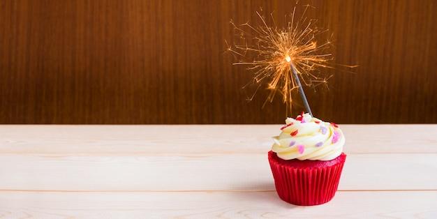 Red velvet cupcake with sparkler lighting over wooden background