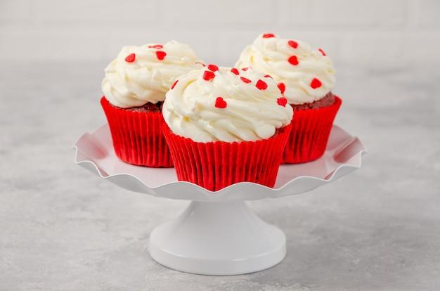 クリームチーズのアイシングと赤いベルベットのカップケーキは、灰色の背景に白いスタンドでバレンタインデーのために飾られています。スペースをコピーします。