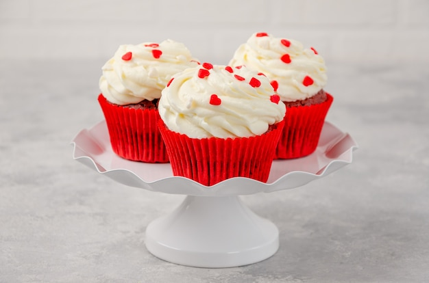 Red velvet cupcakes with cream cheese icing are decorated for valentine's day on a white stand on a gray background. copy space.