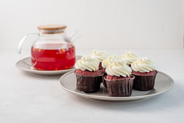 Красные бархатные кексы с белым кремом на вершине.