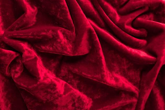 折り目が付いた赤いベルベット生地の質感をクローズアップ