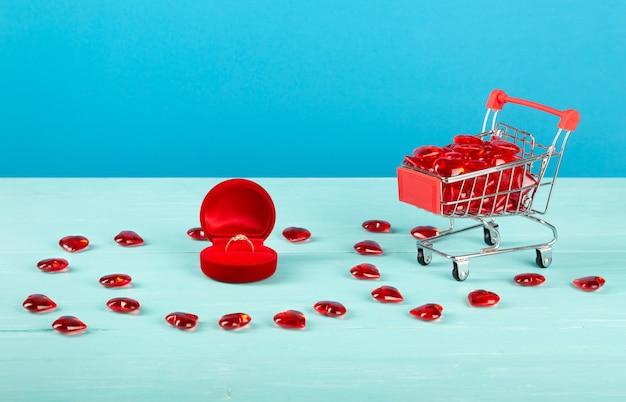 Красная бархатная подарочная коробка с кольцом и сердечной тележкой на синей стене. день святого валентина.