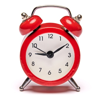 Red vintage alarm clock isolated on white wall with clipping path