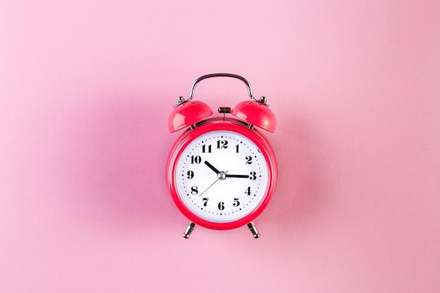 Red vintage alarm clock on light pink color background. time management concept