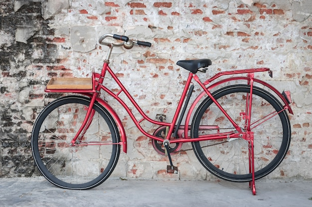 Red vintage bicycle parked in front of brick wall