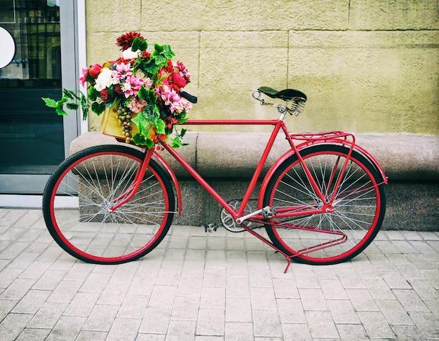 Красный винтажный велосипед с цветочной корзиной