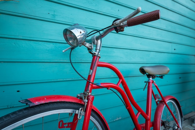 Red vintage bicyle parking on blue wooden wall