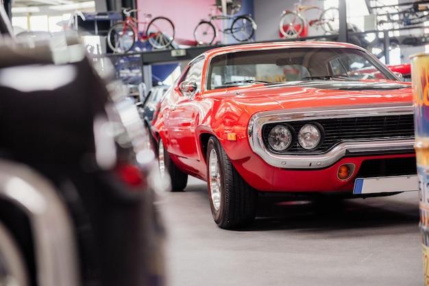 展示会で展示された赤いヴィンテージカーやその他の珍しい車