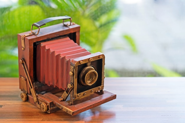 Red vintage film camera - folding pocket camera, vintage accessories on wooden table.