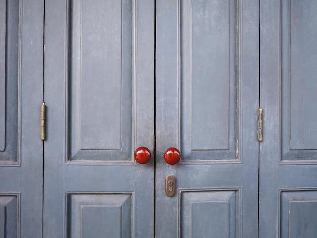 Red vintage knobs on grey wooden door of retro house.