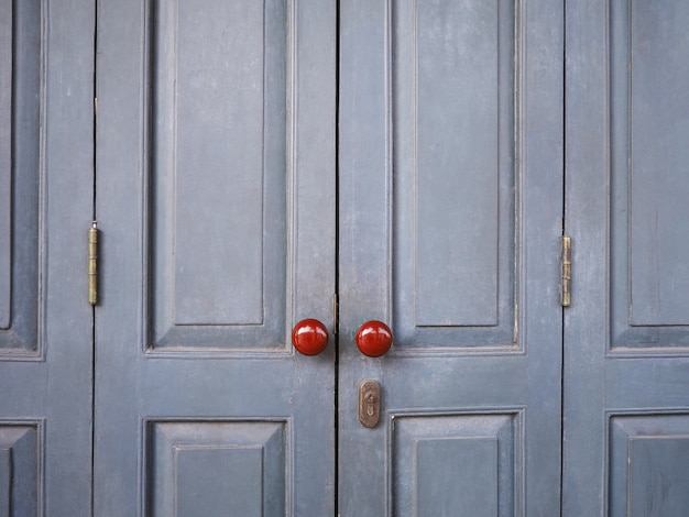 Красные винтажные ручки на серой деревянной двери ретро дома.