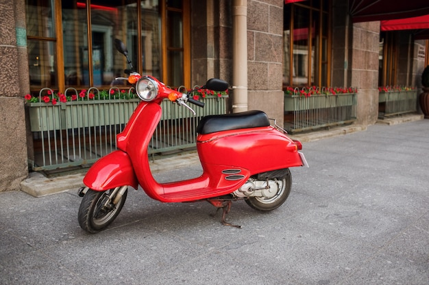 Red vintage scooter parked on sidewalk of empty city street.