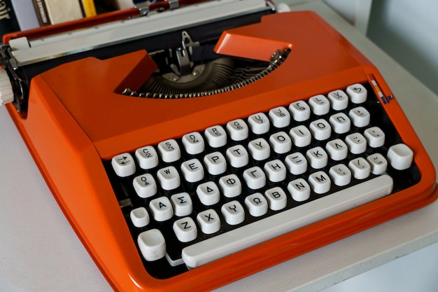 Red vintage typewrite machine with greek alphabet on white table.