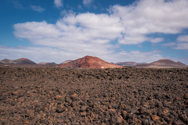Red volcanic landscape, lava scenary with volcano crater in the background